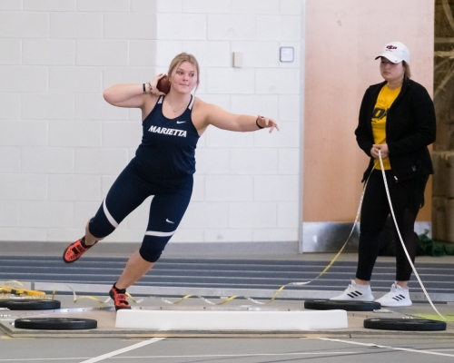 Female student-athlete throwing a shot put