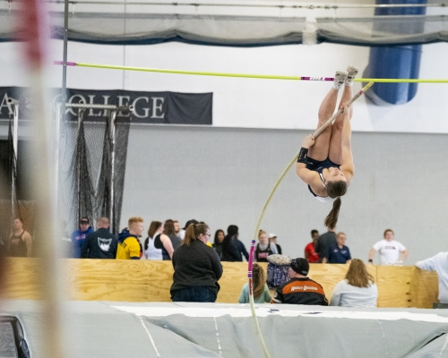 Female pole vaulter getting ready to go over the pole
