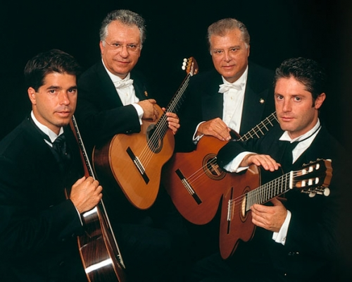 Four men holding guitars