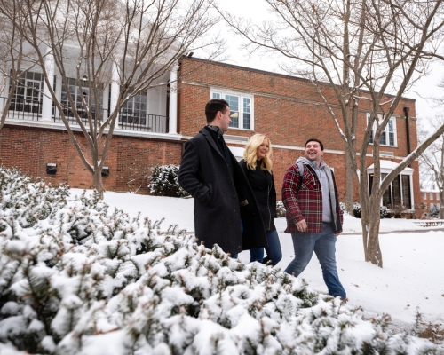 Students walking near Gilman Student Center while it snows