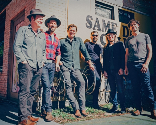 The band Steep Canyon Rangers standing outside a building