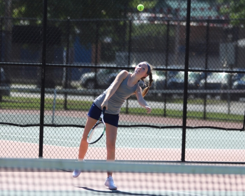 Marietta women's tennis player serving the ball