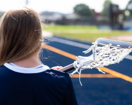 Women's lacrosse player with stick on her shoulder looking at the field