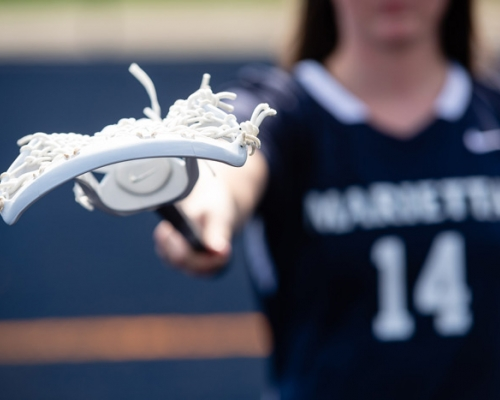Women's lacrosse player holding a stick straight in front of her