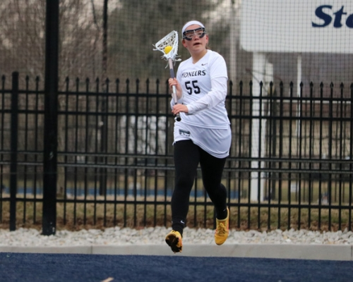 Women's lacrosse player running with her stick in the air