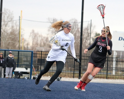 Women's lacrosse player running away from a defender