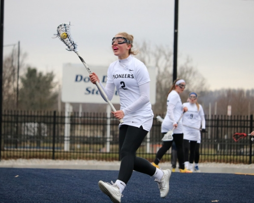 Women's lacrosse player running with stick in the air
