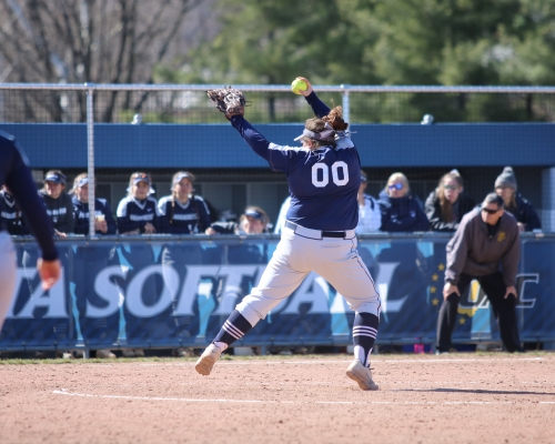 Softball player delivering a pitch to the plate