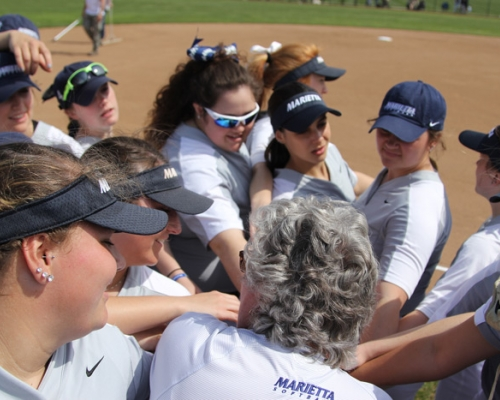 Softball players gathered for a pre-game pep talk