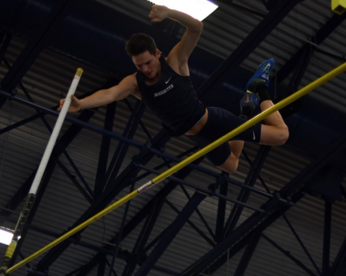Male track athlete competing in the pole vault